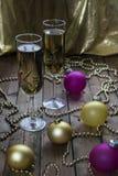 Copas de vino con champán en un fondo de las velas de la Navidad Fotos de archivo libres de regalías