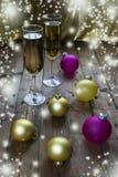 Copas de vino con champán en un fondo de las velas de la Navidad Fotografía de archivo