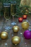 Copas de vino con champán en un fondo de las velas de la Navidad Imagen de archivo libre de regalías