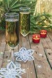 Copas de vino con champán en un fondo de las velas de la Navidad Foto de archivo