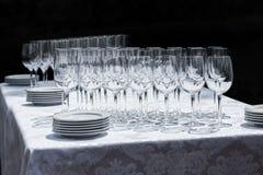 Copas de vino con las placas en la tabla Imagen de archivo libre de regalías