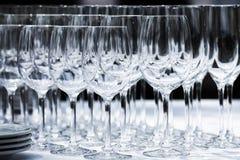Copas de vino con las placas en la tabla Fondo negro Imagen de archivo