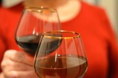 Copas de vino del tintineo en día de fiesta de las manos imagen de archivo