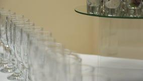 Copas de vino o champán de cristal que se coloca en la tabla con un paño blanco con la placa de cerámica almacen de metraje de vídeo