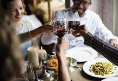 Copas de vino que se aferran de la gente junto en restaurante Fotografía de archivo