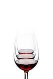 Copas de vino rojas dispuestas y aisladas en el fondo blanco Fotos de archivo