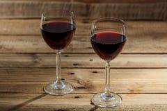 Copas de vino rojas en fondo de madera Imagenes de archivo
