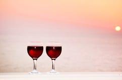 Copas de vino rojas en un fondo de la puesta del sol Imagen de archivo libre de regalías