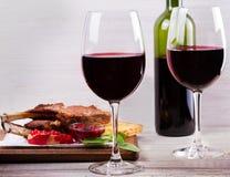 Copas de vino rojas Estante del cordero con la salsa y los verdes de la granada Fotos de archivo libres de regalías