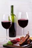 Copas de vino rojas Estante del cordero con la salsa y los verdes de la granada Imagen de archivo