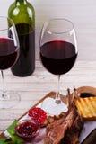 Copas de vino rojas Estante del cordero con la salsa y los verdes de la granada Imagenes de archivo