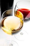 Copas de vino rojas y blancas con la botella negra Foto de archivo
