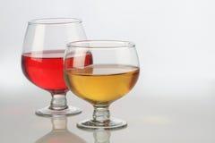 Copas de vino rojas y blancas con la reflexión en blanco Imágenes de archivo libres de regalías