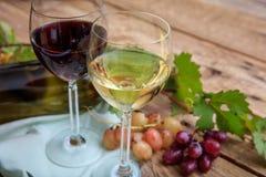 Copas de vino rojas y blancas y uvas frescas en fondo de madera Foto de archivo