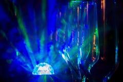 Copas de vino vacías debajo de un champán contra el fondo de luces ligeras Foto de archivo libre de regalías