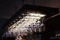 Copas de vino vacías que cuelgan del revés en interior de la barra Fotografía de archivo libre de regalías