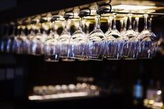 Copas de vino vacías que cuelgan del revés en interior de la barra Imágenes de archivo libres de regalías