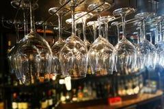 Copas de vino vacías que cuelgan en el estante en barra Fotos de archivo libres de regalías