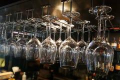 Copas de vino vacías que cuelgan en el estante en barra Imagenes de archivo