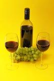 Copas de vino y botella con las uvas Foto de archivo libre de regalías