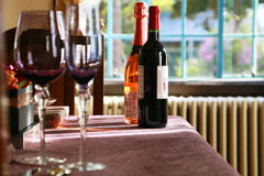 Copas de vino y botellas en la tabla en el cuarto imagen de archivo