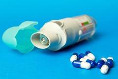 ингалятор и таблетки против астмы на голубой предпосылке Copd стоковые фотографии rf