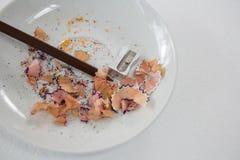 Copeaux colorés avec le crayon et l'affûteuse bruns de couleur dans la soucoupe Photo libre de droits