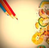 Copeaux et crayons colorés sur le blanc Photos stock