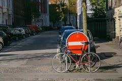 Copenhaga, Dinamarca 6 de maio de 2018: Bicicleta vermelha estacionada na rua da cidade perto do estacionamento de carro e do nen fotos de stock