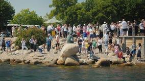 Copenhaga, Dinamarca, em julho de 2018: Uma multidão de turistas é fotografada perto da estátua famosa da sereia pequena dentro filme
