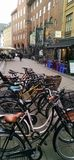 Copenhagen bicycles await owners outside theatre. A row of Danish cycles stand parked on a walking street in downtown Copenhagen in Denmark. A restaurant with royalty free stock photo