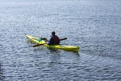 Lonely kayaker paddling in a kayak by the sea rowing, active water sport and leisure, kayaking Stock Image