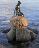 Sculpture of The Little Mermaid on rock, Copenhagen. Copenhagen, Denmark - April 26, 2017: Sculpture of The Little Mermaid on rock is a bronze statue by Edvard stock image