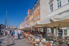 COPENHAGEN, DENMARK - AUGUST 26, 2016: People sit in cafes ad restaurants of Nyhavn districts in Copenhagen, Denma. Rk stock photo