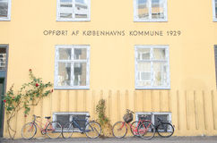 Copenhagen, Denmark - August 25, 2014 - daily view in Conpenhagen, yellow wall, warm sun light, danish word, bike,  near popular a Stock Images