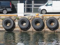Tire boat bumpers in Copenhagen. COPENHAGEN, DENMARK - CIRCA AUGUST 2017: Old tire line on a stone wharf Stock Photography