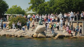 Copenhagen, Denmark, July 2018: A crowd of tourists is photographed near the famous statue of the Little Mermaid in. A crowd of tourists is photographed near the stock footage