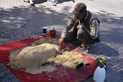 GYSPY MALE CREATING SAND dog SCULPTURE. Copenhagen/Denmark 04 jULY 2018_ Public enjoy watching a Gypsy man creating dog animal with sand sculture on stroeget Royalty Free Stock Photo