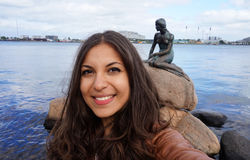 COPENHAGEN, DENMARK - MAY 31, 2017: tourist girl taking selfie photo with the bronze statue of the Little Mermaid. Den lille Havfrue, on the coastal rocks at royalty free stock images