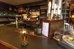 Bar counter with glass of beer, vintage interior, classic style utensils, snacks and bottlers. COPENHAGEN, DENMARK - SEPT 5: Bar counter with glass of beer royalty free stock images