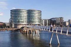 Copenhagen harbor with modern cyclist bridge. Copenhagen, Denmark - September 23, 2016: Modern cyclist bridge Bryggybroen and the Gemini Residence Royalty Free Stock Images