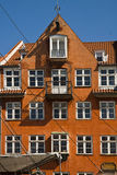 Copenhagen, Nyhavn, antique house with bright colorful facade. View of ancient house facade in Nyhavn harbor with old ship moored in the front. Nyhavn harbor Stock Images
