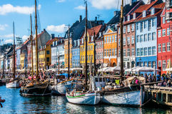 Copenhagen Nyhavn Denmark. Copenhagen, Denmark - November 30, 2014: Crowds of people on the picturesque waterfront of Nyhavn. Coloured historic houses and blue Stock Photos
