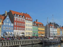 Copenhagen Nyhavn harbour. COPENHAGEN, DENMARK - MARCH 30, 2014: People visiting the Nyhave (meaning New Harbour) 17th century waterfront canal and entertainment Stock Images