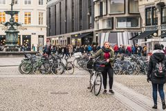 Copenhagen - October 17, 2016: Girls passing by the Local bicycle parking spot in the Amargertorv square.  Stock Photos