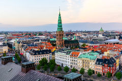 Copenhagen Skyline Panoramic Cityscape. Copenhagen skyline by evening. Denmark capital city streets and danish house roofs. Copenhagen old town and copper spiel Royalty Free Stock Images