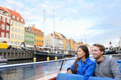 Copenhagen tourists people on boat tour of Nyhavn. Copenhagen tourists people on cruise boat tour on water canal in old port Nyhavn. Young multiracial couple Royalty Free Stock Photo