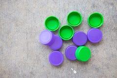 Coperchi a vite di plastica verdi e viola della bottiglia Fotografie Stock Libere da Diritti