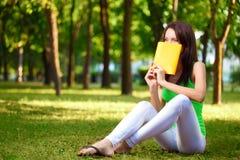 Coperchio della donna il fronte con il libro alla sosta Immagine Stock