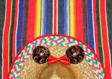 Coperta del poncio del Messico di festa nei colori luminosi con il fondo del sombrero con lo spazio della copia fotografie stock
